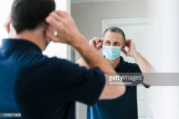 senior businessman adjusts protective face mask before going to work - businesswear stock pictures, royalty-free photos & images