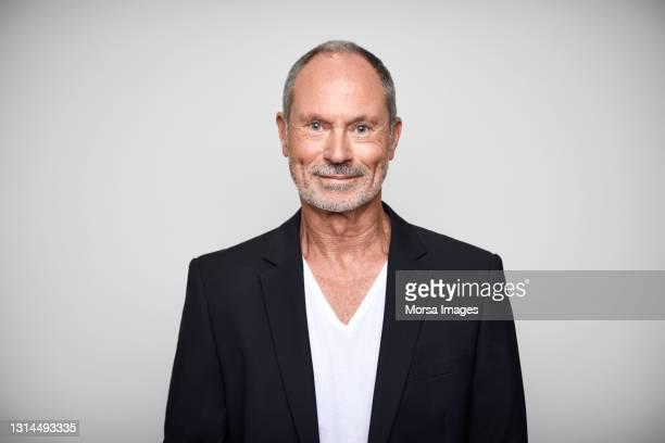 senior businessman against white background - mann 60 jahre stock-fotos und bilder