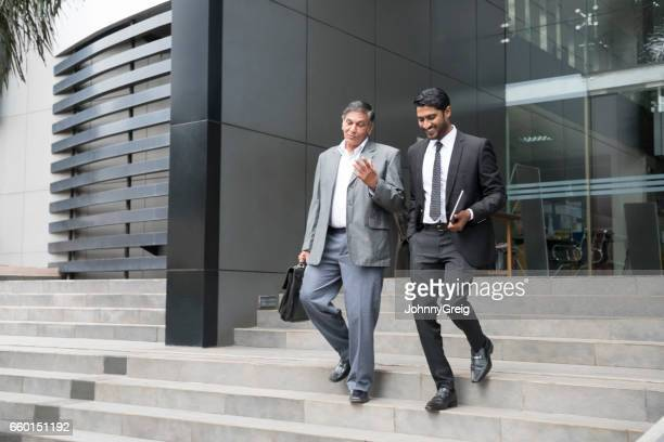 Senior businessman an young male colleague leaving offices