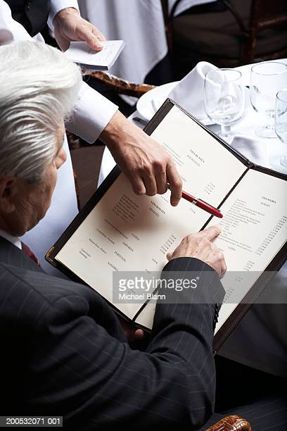 senior businessman and waiter pointing at menu, view over shoulder - menu stock pictures, royalty-free photos & images