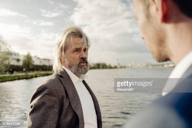senior businessman at a lake talking to man in foreground - successor stock pictures, royalty-free photos & images