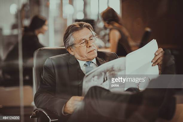 Senior businessman at desk in the office reading newspaper