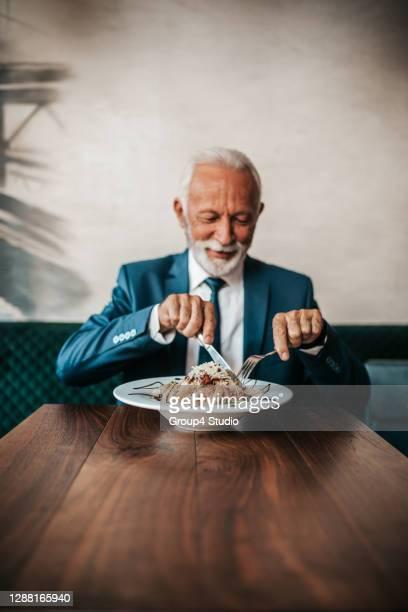 senior businessman at restaurant table - só um homem imagens e fotografias de stock