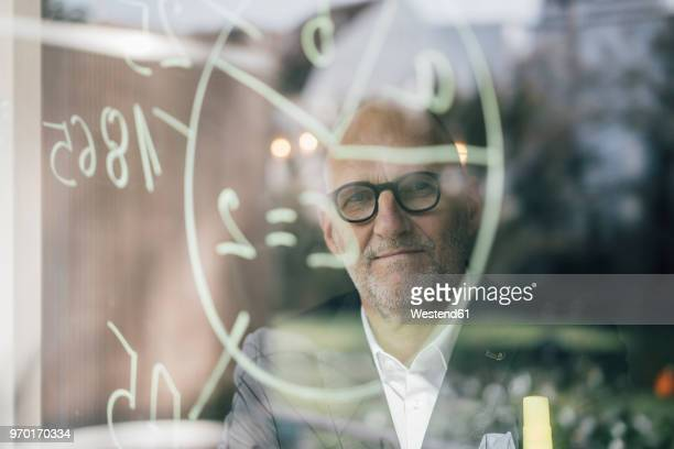 senior businessman brainstorming, drawing formulas on window pane - working seniors stock pictures, royalty-free photos & images