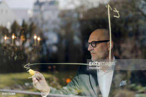 senior businessman brainstorming, drawing formulas on window pane - accounting stock photos and pictures