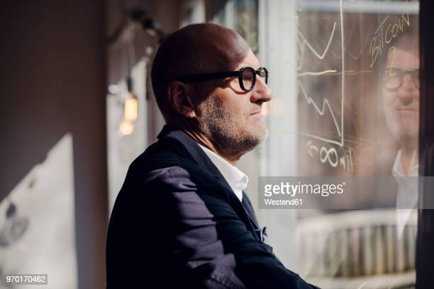senior businessman brainstorming, drawing formulas on window pane - investition stock-fotos und bilder