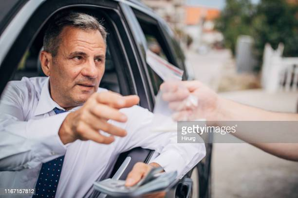 senior businessman buying drugs on the street - drug abuse stock pictures, royalty-free photos & images