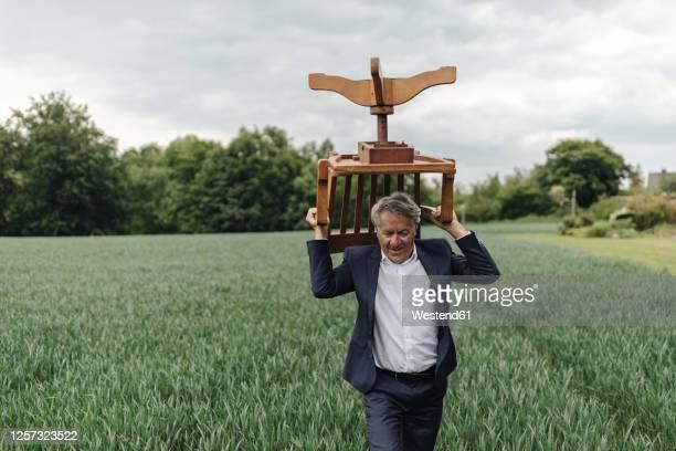 senior businessman carrying a chair on a field in the countryside - tragen stock-fotos und bilder