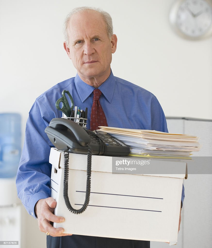 Senior businessman carrying box of office items : Stock Photo