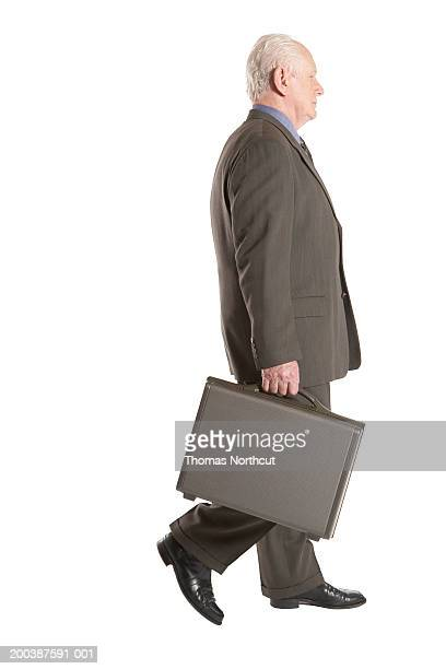 senior businessman carrying briefcase, side view - brown suit stock photos and pictures