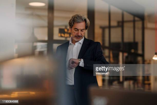 senior businessman checking the time in office - watch timepiece stock pictures, royalty-free photos & images
