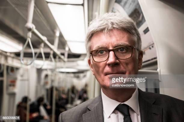 Senior businessman commuting inside a tube train carriage on London underground, UK