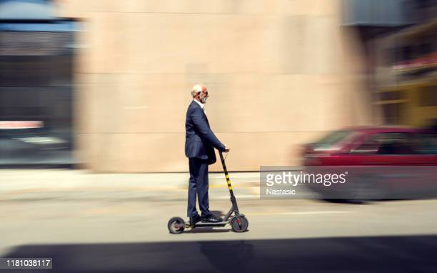 senior businessman cruising on a scooter through city - working seniors stock pictures, royalty-free photos & images