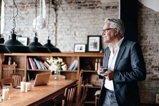 Senior businessman drinking coffee, smiling - gettyimageskorea