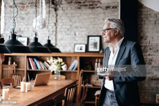 senior businessman drinking coffee, smiling - business owner stock photos and pictures