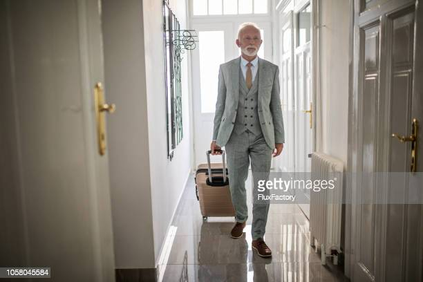 senior businessman entering his hotel apartment - rich old man stock photos and pictures