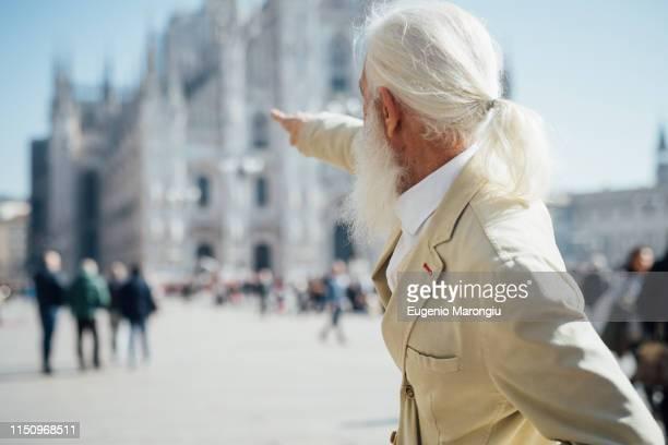 senior businessman exploring city, milan cathedral in background, milano, lombardia, italy - duomo di milano foto e immagini stock
