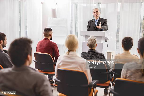 Senior businessman giving a speech on a conference.
