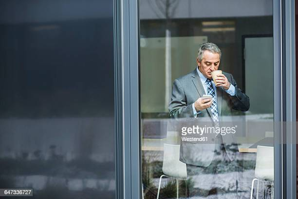 Senior businessman holding coffee to go looking on cell phone