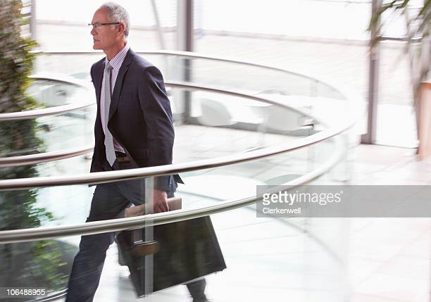 Senior businessman in a hurry with briefcase in lobby