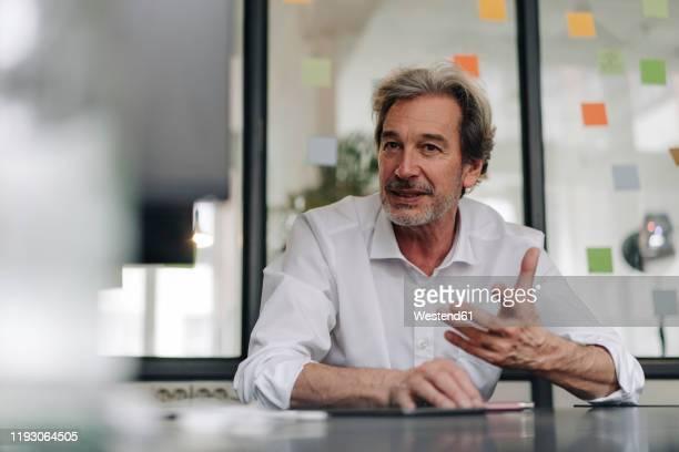 senior businessman in conference room in office - reden stock-fotos und bilder