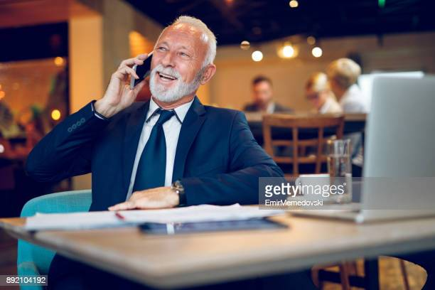 Senior businessman in internet cafe talking on the phone