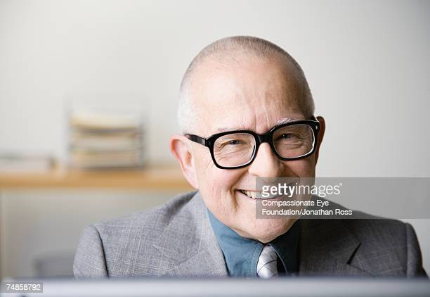 senior businessman in office, smiling, close-up, portrait - compassionate eye foundation stock pictures, royalty-free photos & images