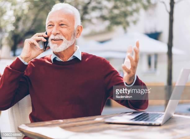senior zakenman in sidewalk café praten aan de telefoon - goed nieuws stockfoto's en -beelden