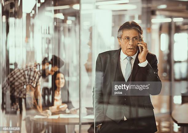 Senior businessman in the office  using mobile phone