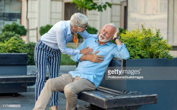 senior businessman is having a heart problems in the city street - heart attack stock pictures, royalty-free photos & images