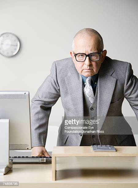 senior businessman leaning on desk in office, portrait - completamente calvo foto e immagini stock