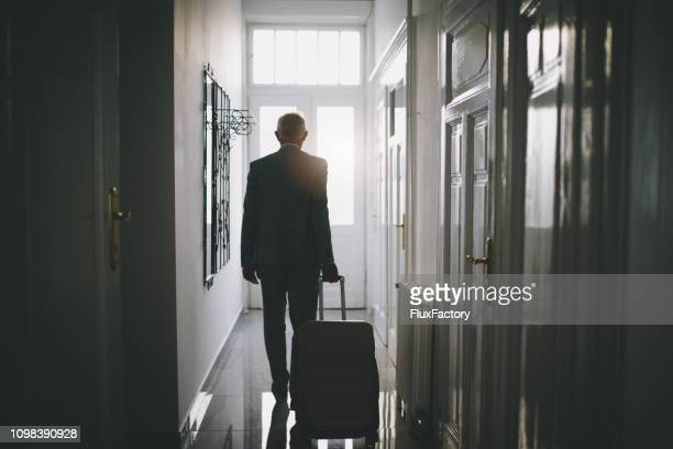 senior businessman leaving his hotel room - disembarking stock pictures, royalty-free photos & images