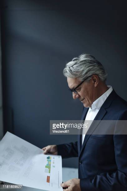 senior businessman looking at papers - business finance and industry stock-fotos und bilder