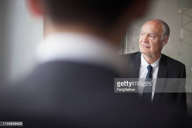 senior businessman looking away at office meeting - successor stock pictures, royalty-free photos & images