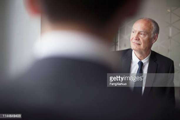 オフィス会議を見ている先輩ビジネスマン - 後任 ストックフォトと画像