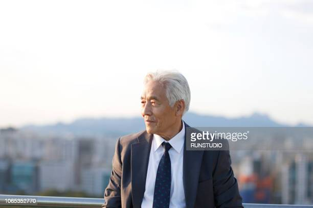 Senior businessman looking away on rooftop