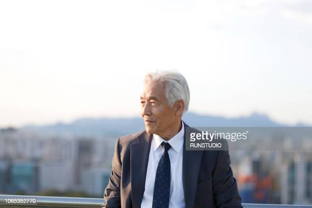 Senior businessman looking away on rooftop