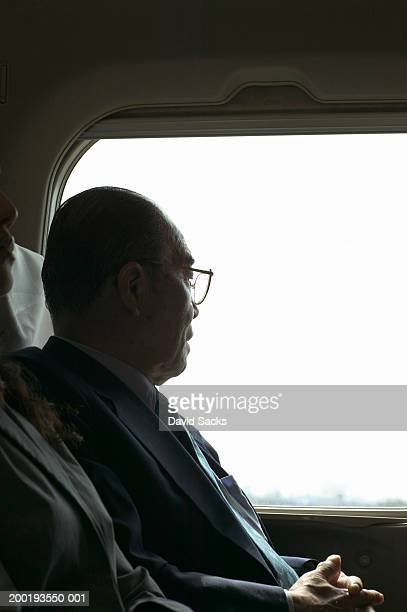 Senior businessman looking out of train window, side view
