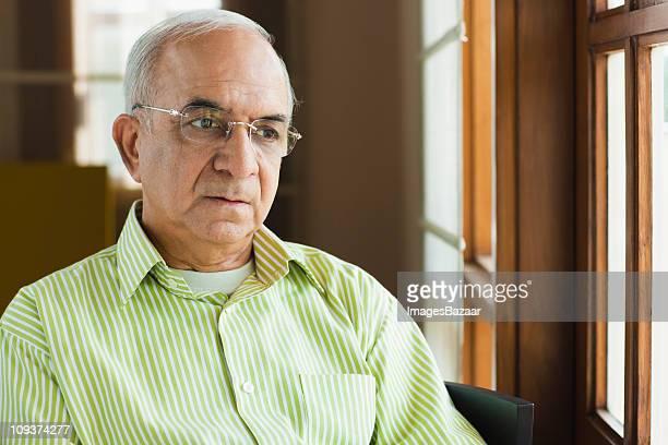Senior businessman looking through window