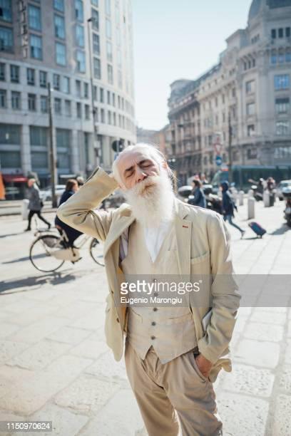 senior businessman lost in city, milano, lombardia, italy - hände hinter dem kopf stock-fotos und bilder