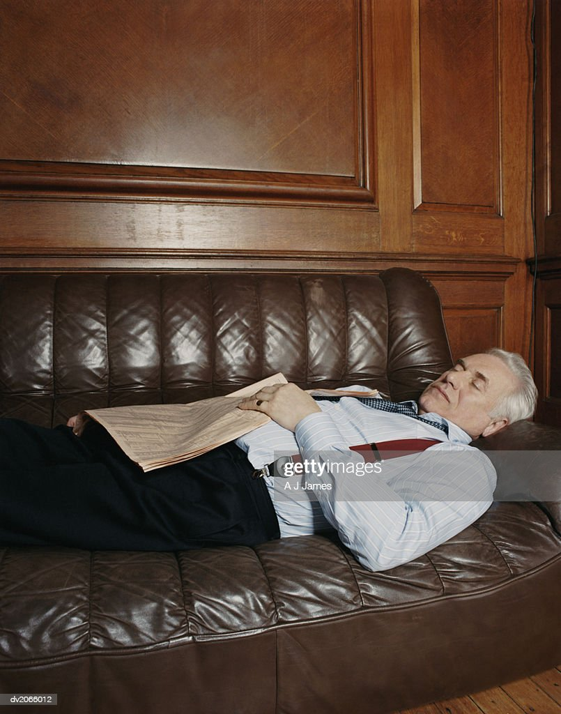Senior Businessman Lying Asleep on a Leather Sofa Holding a Newspaper : Stock Photo