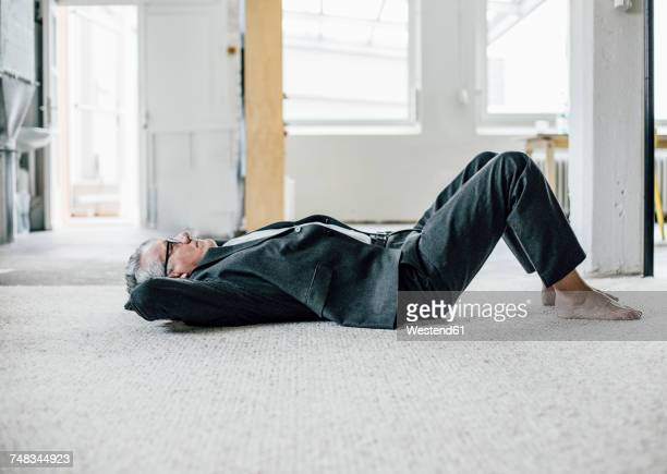 senior businessman lying on the floor - lying down stock pictures, royalty-free photos & images