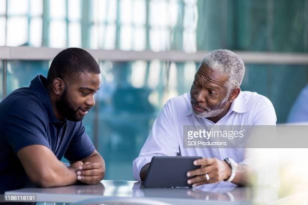 シニアビジネスマンは、男性のコロージュと会う - 宅地 ストックフォトと画像