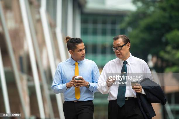 senior businessman mentoring a millennial businessman - idol stock pictures, royalty-free photos & images