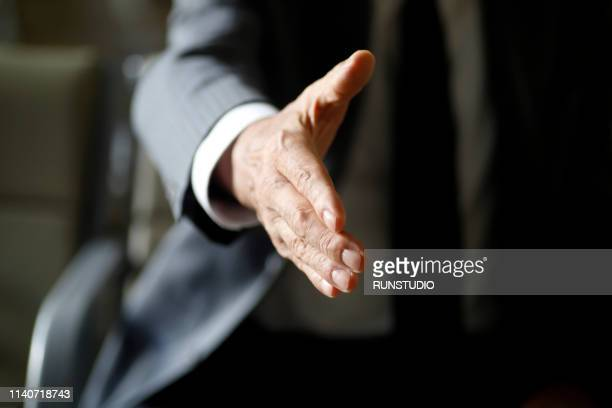 senior businessman offering handshake - gesturing stock pictures, royalty-free photos & images