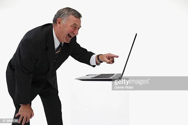 Senior businessman pointing at laptop computer, laughing