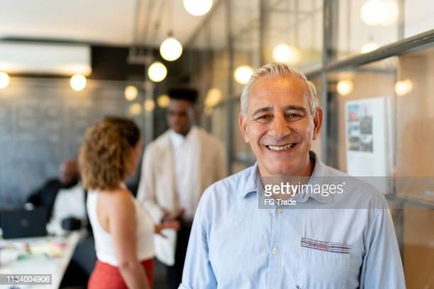 senior zakenman portret bij startup modern office - latijns amerikaanse en hispanic etniciteiten stockfoto's en -beelden