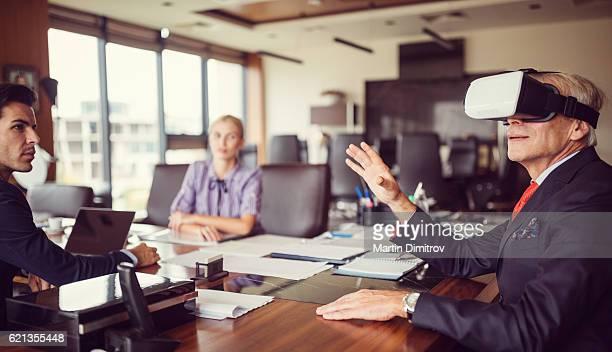 Senior businessman presenting virtual reality simulator at business meeting