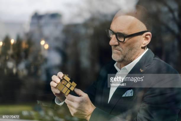senior businessman putting together puzzle cube - geduld stock-fotos und bilder
