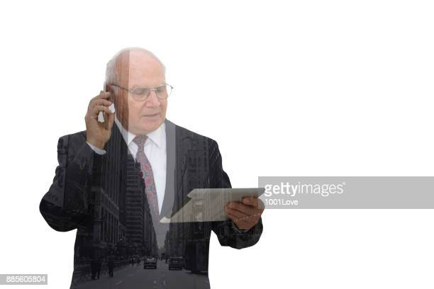 Senior businessman reading a message on his digital tablet and talking on phone